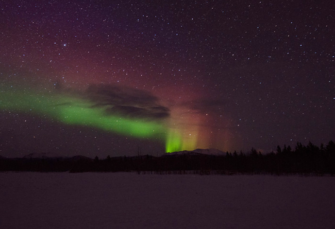 Aurora Borealis, or the Northern Lights appear bright in the night sky.