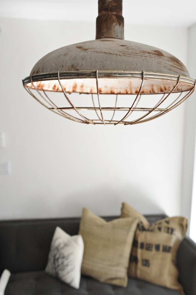 Industrial lighting like this pendant pulled from a local movie set gives wing and kevins condo instant personality